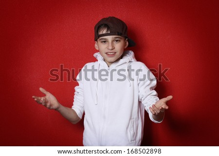 Young bully man teen in cap throws up his hands in asking red background