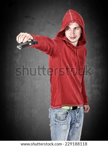 young burglar with gun in hand on black background - stock photo