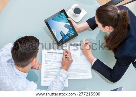 Young business couple discussing rental agreement. Woman showing man office buildings on digital tablet at table. - stock photo