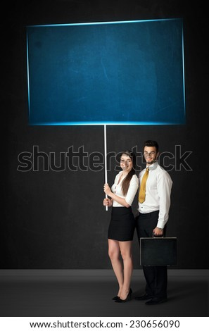 Young business couple holding a big, blue board  - stock photo
