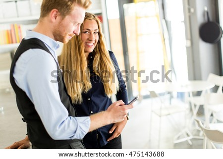 Young business couple looking at the phone in the office