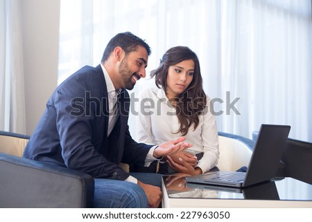 Young business couple meeting with tech devices - stock photo