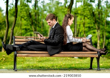 Young Business couple sitting on the bench and reading or working with tablets outdoors. - stock photo