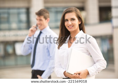 Young business couple standing in front of the building. Business woman carrying laptop while her partner use a mobile phone for business conversation. - stock photo
