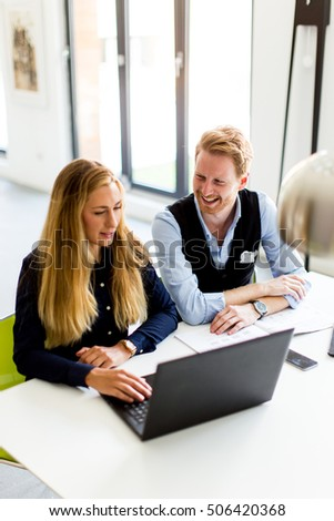 Young business couple using laptop in the office