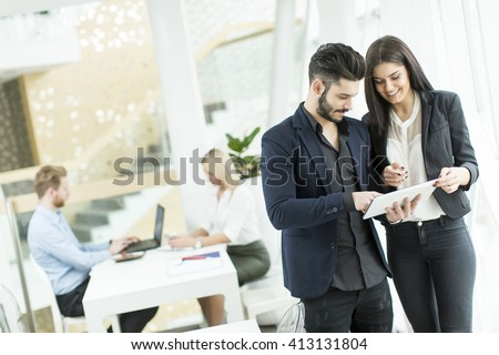 Young business couple using tablet in the office - stock photo
