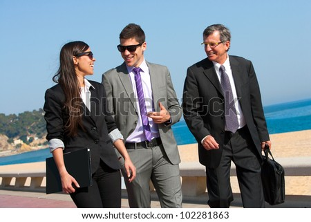 Young business couple walking with colleague outdoors.