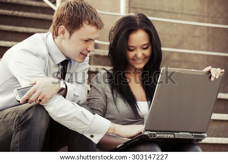 Young business couple with laptop on the steps