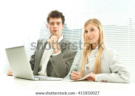 Young business couple work laptop with venetian blind window background