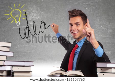 young business drawing a light bulb on his black board meaning he is having a great idea