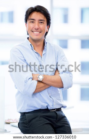 Young business executive at the office with arms crossed - stock photo