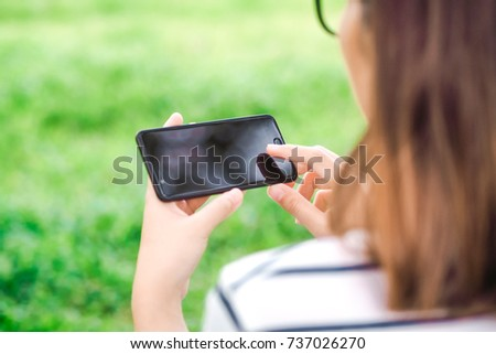 Young business female using smart phone while she is relaxing in Park in the fresh air