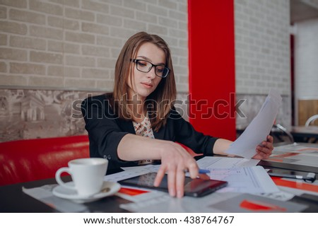Young business girl sitting at the bar, and she's working on and his work