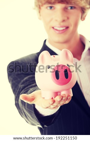 Young business holding piggy bank - stock photo
