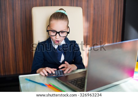 Young business lady girl in glasses surprised at the table with laptop computer and calculator - stock photo