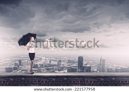 Young business lady on top of building with umbrella