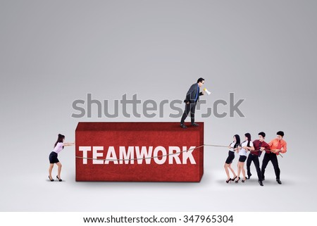 Young business leader leads his team to work together and remove a business hurdle - stock photo