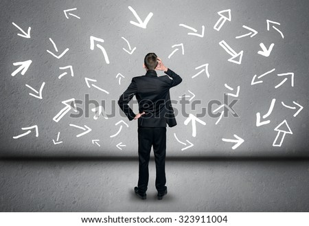 Young business man and arrows pointing directions - stock photo