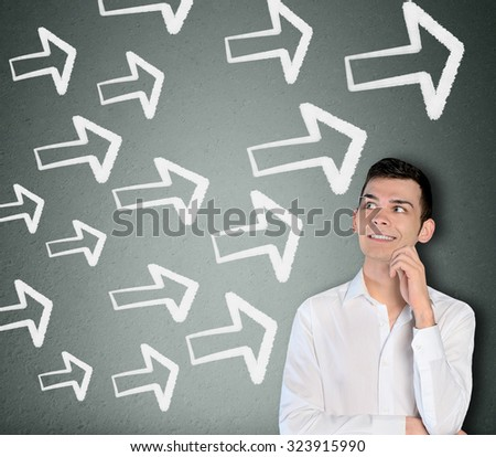 Young business man and arrows pointing right - stock photo