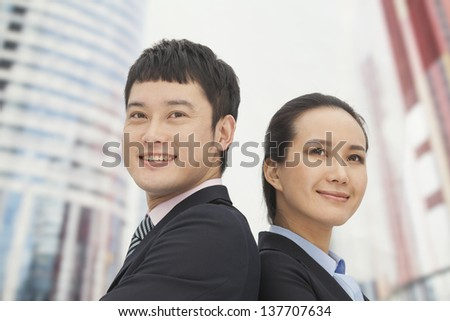 Young business man and woman standing back to back
