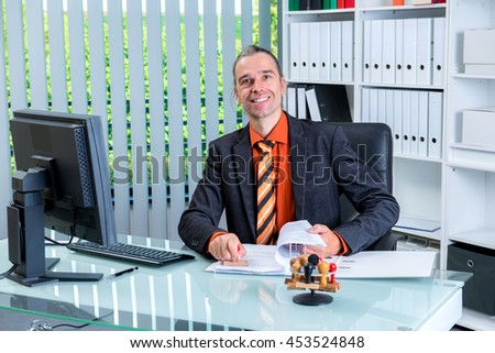 young business man at his desk looking friendly in to the camera - stock photo