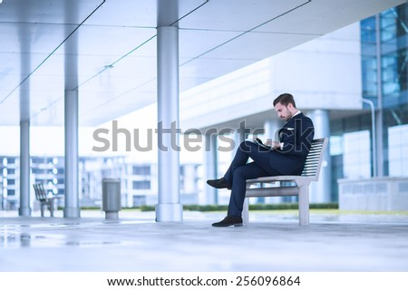 young business man at office building reading newspaper.  - stock photo