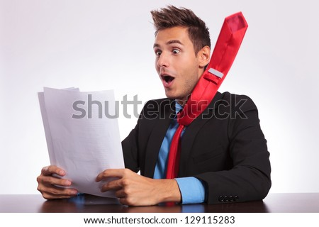 young business man at the office reading something spectacular from some paper sheets, remaining stunned with his tie flying away