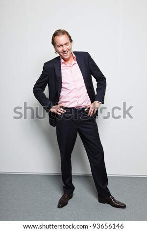 Young business man blond hair wearing blue suit and pink shirt isolated on white background.