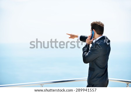 Young business man calling by cell phone on white beach