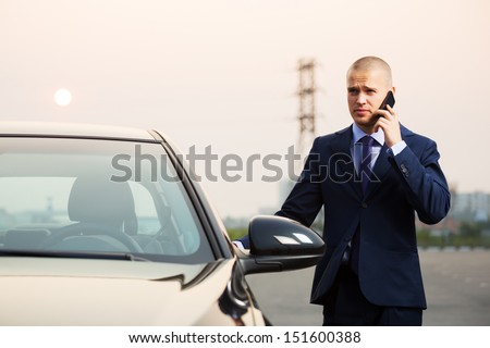 Young business man calling on the phone at the car - stock photo