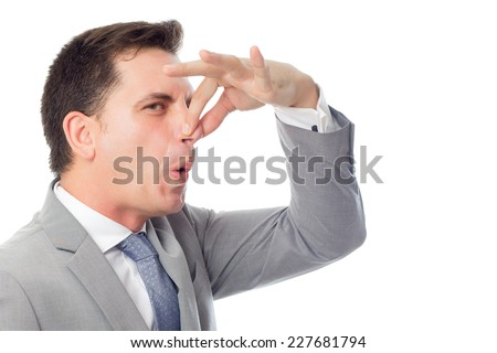 Young business man close up over white background. Grabbing his nose with his fingers - stock photo