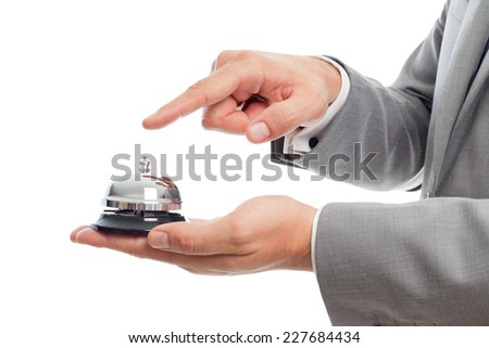 Young business man close up over white background. Using a hotel bell