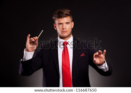 young business man conducting with a stick, while looking at the camera. on dark background - stock photo