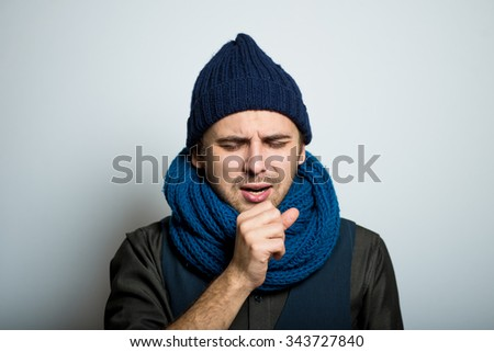 young business man coughed into his fist, winter style clothes, studio shot isolated on the gray background - stock photo
