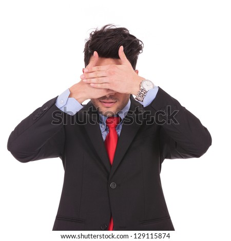 young business man covering his eyes with both his hands, on white background - stock photo