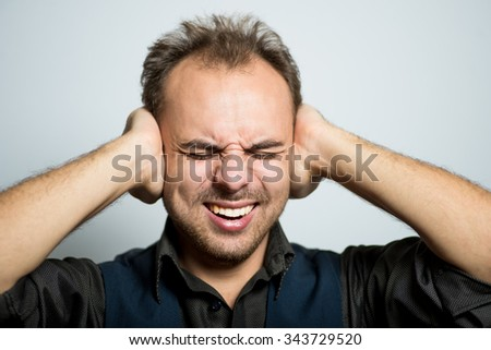 young business man covers his ears with his hands, manager, office style studio shot isolated on the gray background - stock photo
