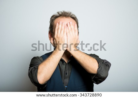 young business man covers his face, manager, office style studio shot isolated on the gray background