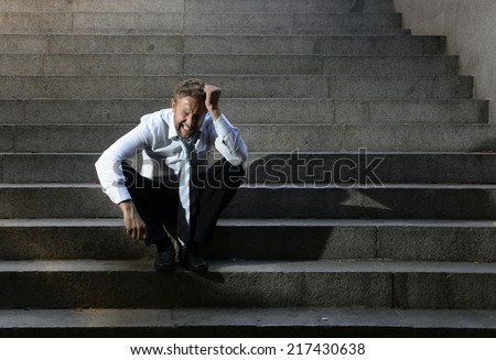 Young business man crying abandoned lost in depression sitting on ground street concrete stairs suffering emotional pain, sadness, looking sick in grunge lighting - stock photo