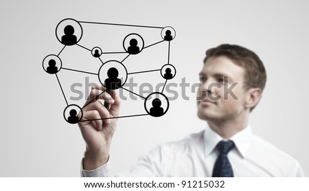 Young business man drawing a social network or globalization concept. Man drawing a global network on a glass window. On a gray background. - stock photo