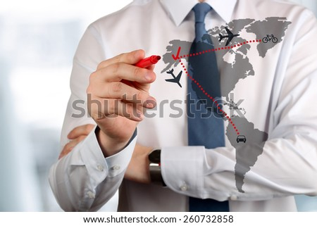 Young business man drawing an airplane routes on world map.  - stock photo