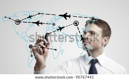 Young business man drawing an airplane routes on world map. Man drawing world map with aircraft flying on a glass window. The metaphor of international air travel around the world - stock photo