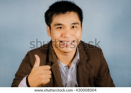 Young business  man gives thumbs up on blurred background - stock photo