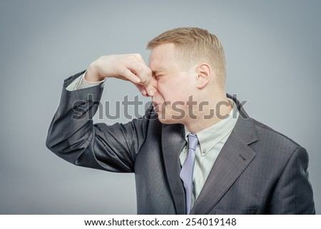 Young business man . Grabbing his nose with his fingers - stock photo