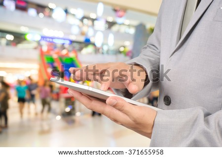 Young Business Man Hands holding Tablet in Shopping Mall or Department Store. - stock photo