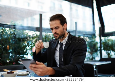 Young business man having a breakfast sitting on beautiful terrace with plants, handsome man in suit read news holding digital tablet pc in the hands - stock photo