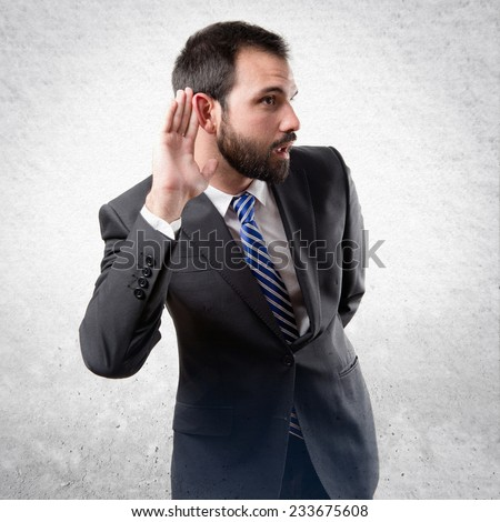 Young business man hearing something over textured background  - stock photo