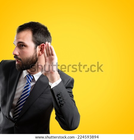 Young business man hearing something over yellow background  - stock photo