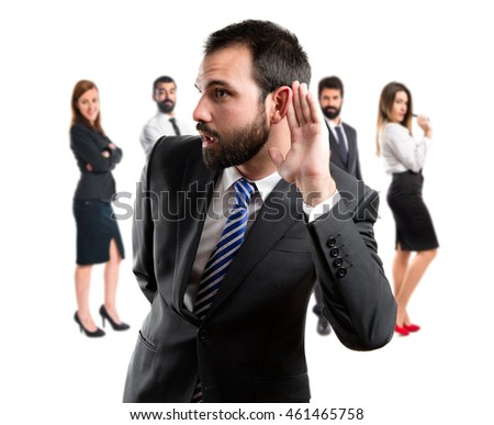 Young business man hearing something with many people behind
