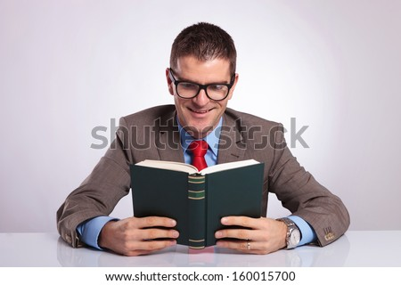 young business man holding a book with both hands and smiling while reading from it. on a gray background