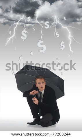 Young business man holding an umbrella under a storm of money